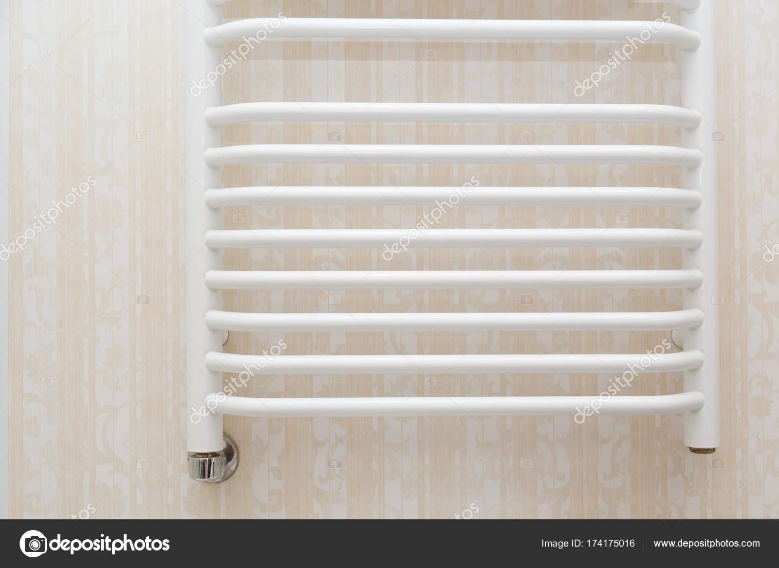Termoarredo bianco su piastrelle di travertino in bagno moderno