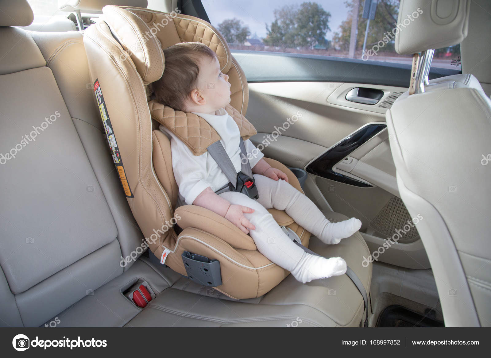 enfant dans un si ge d auto de b b de fixation isofix si ge auto beige dans un salon lumineux. Black Bedroom Furniture Sets. Home Design Ideas