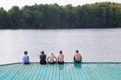 Fényképek Gyermekkor és a barátság. Öt fiú úszónadrág ül a mólón, a folyó, a háttérben az a erdő egy napsütéses nyári nap