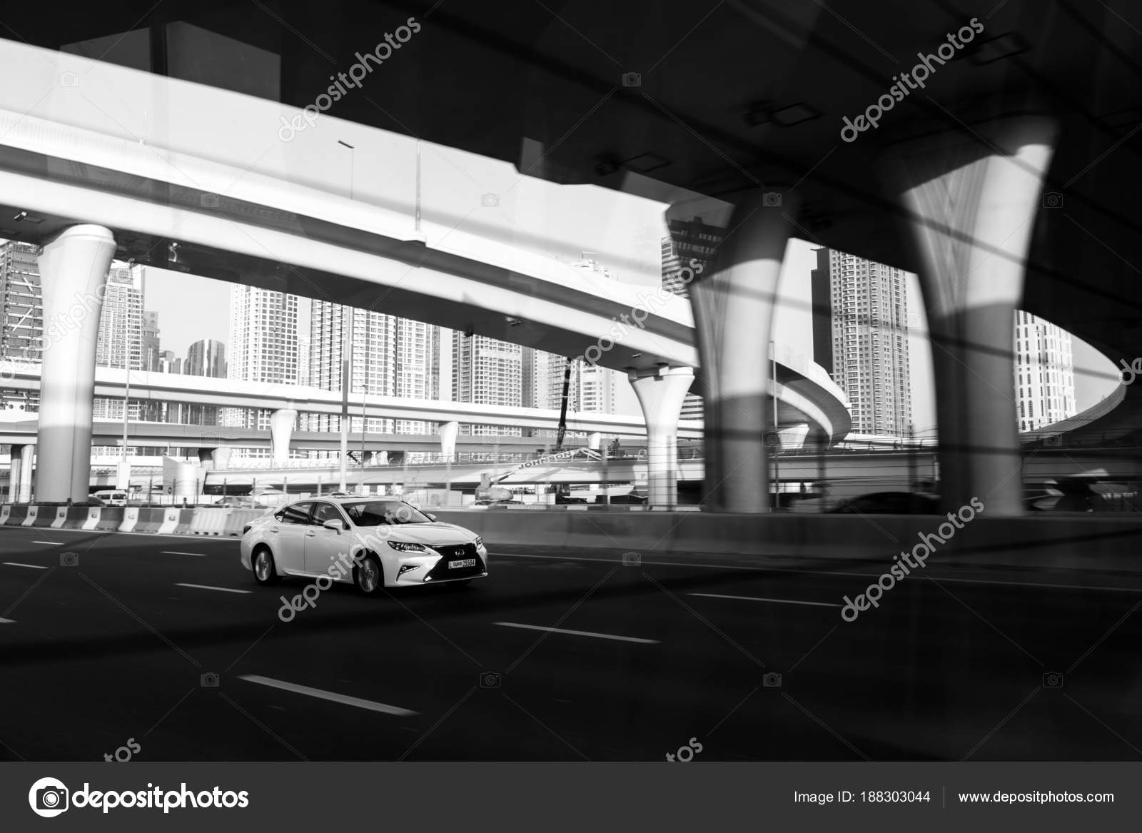 Dubai uae february 20 2018 lexus rides on the highway against the backdrop of road junctions and overpasses black and white photo photo by