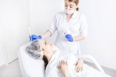 A female cosmetician doctor works with a young girl's patient and applies a cream on her face. Concept of a beauty and skin care. Cosmetic procedures and rejuvenation session