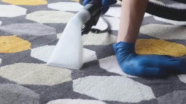 Úklidová služba. Muž údržbář v rukavicích a jednotném vakuu čistý koberec s profesionálním vybavením