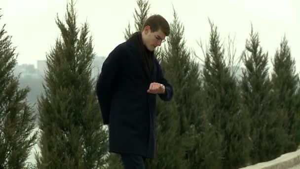 Muž nervózně čeká a dívá se na hodinky