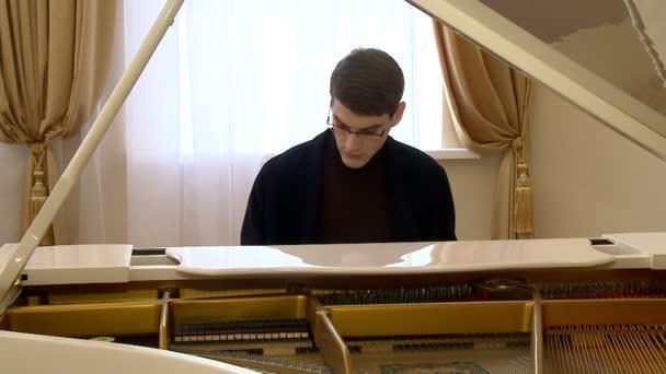 fiatal zongorista-val szemüveg egy fehér grand zongora