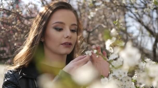 Young pretty smiling caucasian woman standing near blooming spring tree.
