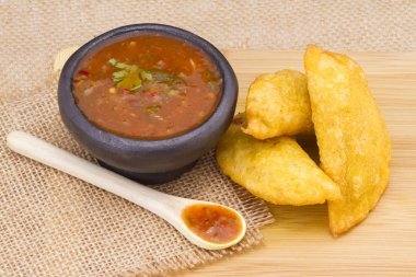Colombian empanada with spicy sauce on wooden background
