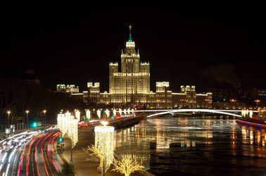 Evening view on the high-rise building of the Kotelnicheskaya embankment and Big Ustinsky bridge. Christmas illuminations on Moskvoretskaya embankment, Moscow, Russia
