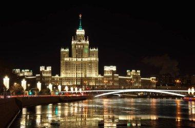 Evening view on the high-rise building of the Kotelnicheskaya embankment and Big Ustinsky bridge. Christmas illuminations on Moskvoretskaya embankment, Moscow, Russia