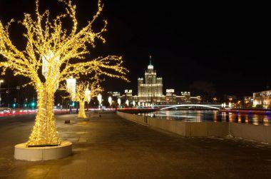 Christmas illuminations on Moskvoretskaya embankment, Moscow, Russia. Evening view on the high-rise building of the Kotelnicheskaya embankment and Big Ustinsky bridge