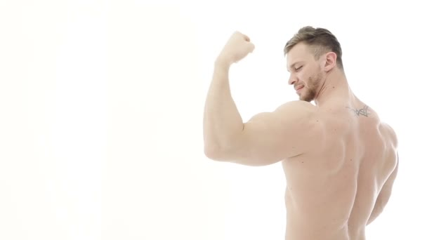 Bodybuilder flexing his muscles. Athlete demonstrates biceps and winks