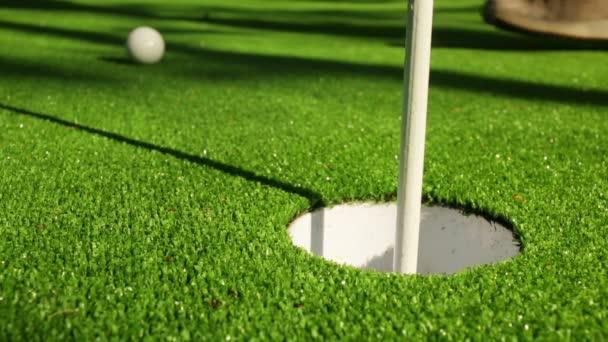 Detailní záběr golfista pomocí putter ponořit krátký putt do díry