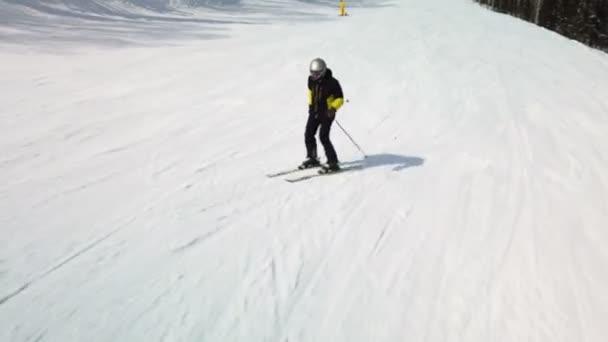 Der junge erwachsene Freizeitskifahrer genießt im kalten Winter das idyllische Perfekt-Wetter. Skifahren auf perfekt präparierter Skipiste im Skigebiet