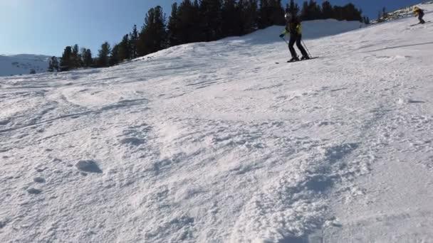 Der junge erwachsene Freizeitskifahrer genießt im kalten Winter das idyllische Perfekt-Wetter. Skifahren allein auf einer perfekt präparierten Skipiste im Skigebiet. auf dem Gipfel des Berges