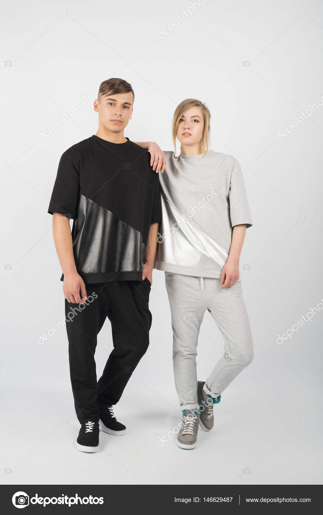 7b7465c6405 Αγόρι και κορίτσι. Νεαρός μυώδης άνδρας φορώντας μαύρα ρούχα και αθλητικά  παπούτσια με κορίτσι με γκρίζα ρούχα που απομονώνονται σε λευκό φόντο —  Εικόνα από ...