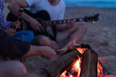 friends sitting on the beach. man is playing guitar.