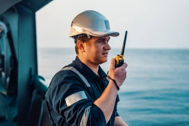 Marine Deck Officer or Chief mate on deck of offshore vessel or ship , wearing PPE personal protective equipment - helmet, coverall. He holds VHF walkie-talkie radio in hands.