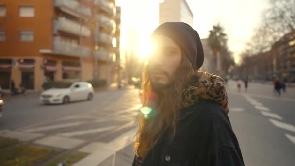 Portrait of long haired hipster walking on street in modern city