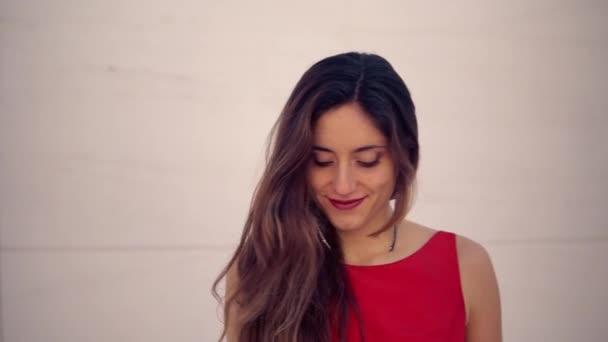Beautiful woman in red elegant dress. Urban white background