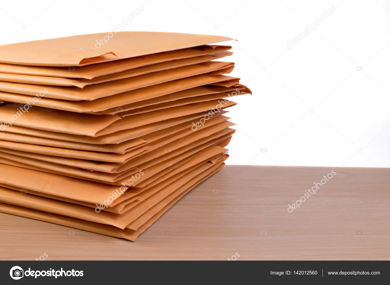 stack of bubble wrap padded mailing envelopes and pen on white