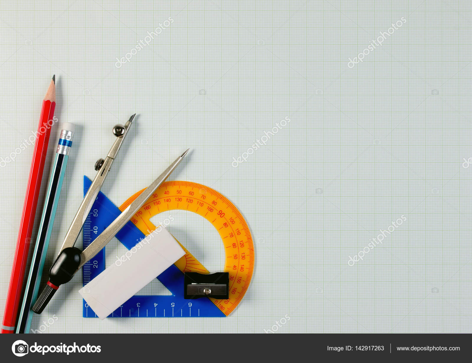Mathematical instruments over the corner of a math graph paper with ...