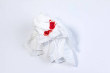 Wound blood, blood on tissue paper on white background. Nosebleed or epistaxis treatment blood in tissue paper. Health medical.
