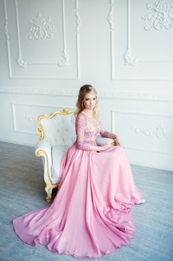 Beautiful blonde woman in evening pink dress. Classic white interior.