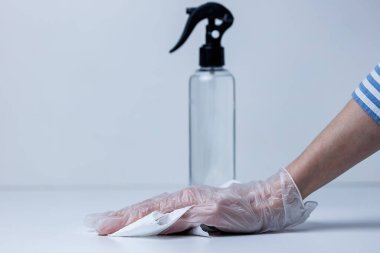 female hand in a glove disinfects the surface with sanitizer.