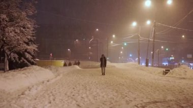 pedestrians hurry along sidewalk under abnormal snowfall in the evening
