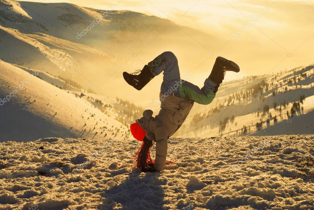 girl in acrobatic pose standing on a mountain top at sunset