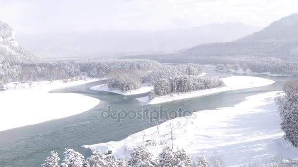 Letecký pohled. Let nad krásné zimní řeka a zasněžený les. Příroda v zimě. Panorama krajiny. Altaj, Sibiř