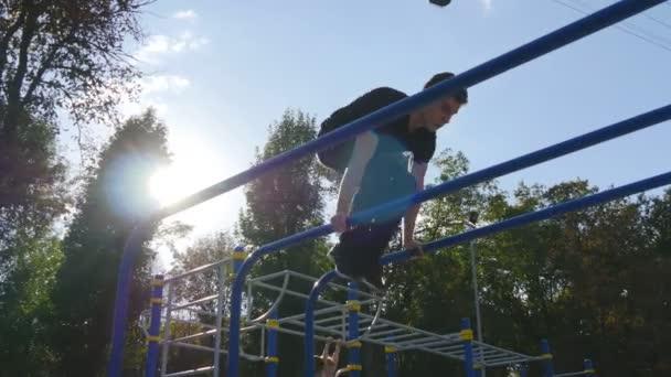 Atletický muž dělá gymnastické prvky na baru v městském parku. Mužské sportovce provádí silová cvičení během cvičení venkovní. Mladý kluk ukazuje statické cvičení. Zdravý životní styl