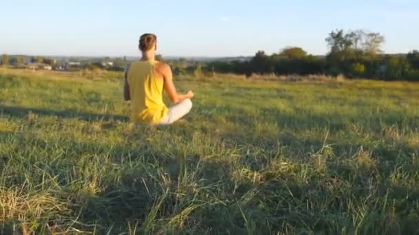 Young man sitting in yoga pose at green grass in the meadow and meditates. Muscular guy relaxing in lotus pose at nature. Recreation outdoor at sunny day. Beautiful landscape at background. Close up