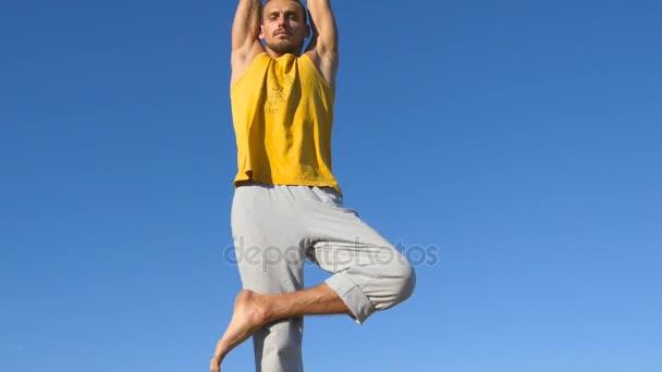 Porträt eines jungen, sportlichen Mannes, der am Baum steht und mit blauem Himmel als Hintergrund posiert. Kaukasier, der Yogabewegungen und Positionen in der Natur praktiziert. Sportler balanciert auf einem Bein. Gesunder aktiver Lebensstil