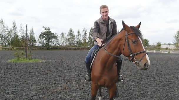 männliche Jockey Reiten oben sitzen und streichelt und streichelt den Hals des Tieres. junger Mann streichelt Pferdemähne im Freien. Fürsorge und Liebe für die Tiere. Zeitlupe in Nahaufnahme