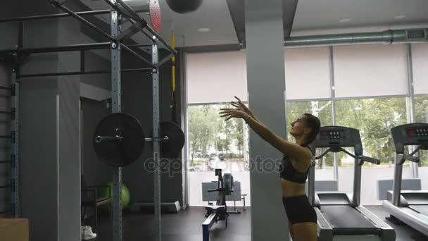 Mladá silná žena s tělem ideální fitness v sportovní cvičení s medicinbal v tělocvičně. Holka dělá crossfit tréninku. Atletka dřepy během cvičení vnitřní. Zpomalený pohyb. Detailní záběr