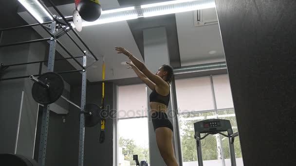 Fiatal erős nő, tökéletes fitness test gyakorlása során a gyógyszer labda edzőteremben sportruházat. A lány csinál a crossfit edzés. Női sportoló zömök, fedett edzés közben. Lassú mozgás. Közelről