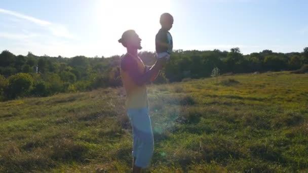 Der junge Vater spielt mit seinem Kind in der Natur. Papa hält seinen Söhnen die Beine hin und wirft sie nach draußen. glückliche Familie, die Zeit zusammen draußen auf der Wiese verbringt. schöne Landschaft im Hintergrund. Nahaufnahme