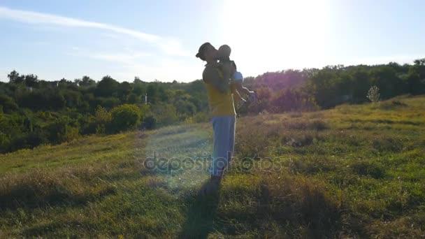 Mladý otec jeho malého syna do vzduchu vyhazování a chytání ho do rukou venkovní. Táta hrál s jeho dítětem v přírodě. Šťastná rodina spolu trávili čas venku na louce. Krásné pozadí