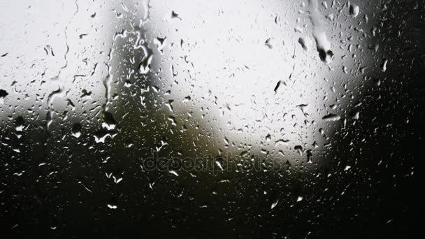 Detail z kapky vody na skle. Kapky deště na okenní sklo s rozostření pozadí. Rozmazané strom a obloha. Deštivé dny, déšť stékající okno, bokeh