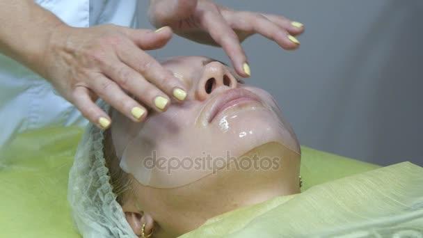 Kosmetička, použití obličejové masky na obličeji krásnou dívku na salon krásy. Žena s péči o obličej. Použití masky v kosmetologii. Detail mladé ženy s Silikonová maska na obličej