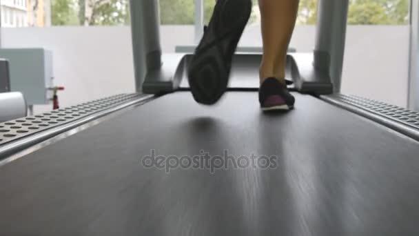 Weibliche Beine auf Laufband im Fitnessstudio. Junge Frau Ausübung während der Cardio-Training. Füße von Mädchen in Ausbildung im Sportclub indoor Sportschuhe. Nahaufnahme