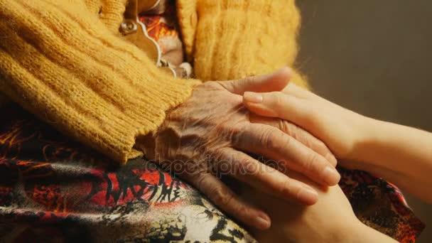 Stará žena mladá žena drží ruku vrásek zblízka