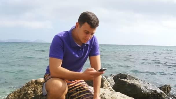 Mladý muž sedí na kámen a používání telefonu v blízkosti moře. Portrét pohledný chlap s mobilním telefonem na ocean beach. Chlapec při pohledu na telefon app. On textových zpráv sms nebo chatování v sociální síti