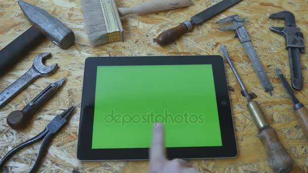Držby tablet pc v režimu na šířku s tabulkou workshop s tesařské nářadí v pozadí. Člověk ruku tabletu pomocí zeleným plátnem. Pohled shora