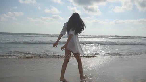 Šťastná žena kráčí a točí se na pláži u oceánu. Mladá krásná dívka těší život a baví se na mořském pobřeží. Letní dovolená nebo dovolená. Přírodní krajina na pozadí. Zpomalený pohyb