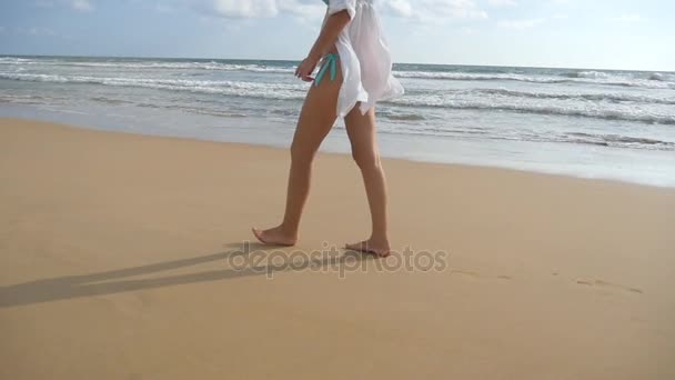 Beautiful woman in swimsuit walking on sea beach barefoot. Young girl going on the ocean shore. Female foot stepping on the sand with sea waves background. Summer vacation concept. Slow motion
