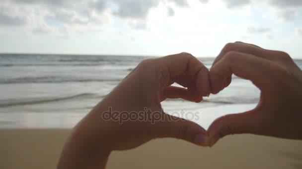 Mädchen, das Herz mit ihren Händen über Meeresgrund mit schönem goldenem Sonnenuntergang macht. Silhouette eines weiblichen Armes in Herzform mit Sonnenaufgang im Inneren. Ferienkonzept. Sommerurlaub am Strand. Zeitlupe