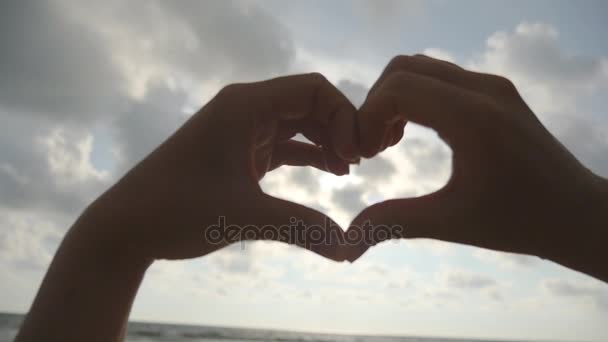 Dívka, takže srdce s rukama nad moře pozadí s krásný zlatý západ slunce. Silueta ženy rameno ve tvaru srdce s východem slunce uvnitř. Koncept dovolenou. Letní dovolená na pláži. Zpomalený pohyb