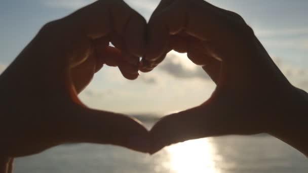 Lány, így a szív vele a tenger a háttérben a gyönyörű golden sunset átadja. Sziluettjét női kar, a szív alakú a sunrise belül. Nyaralás koncepció. Nyaralás a tengerparton. Lassú mozgás