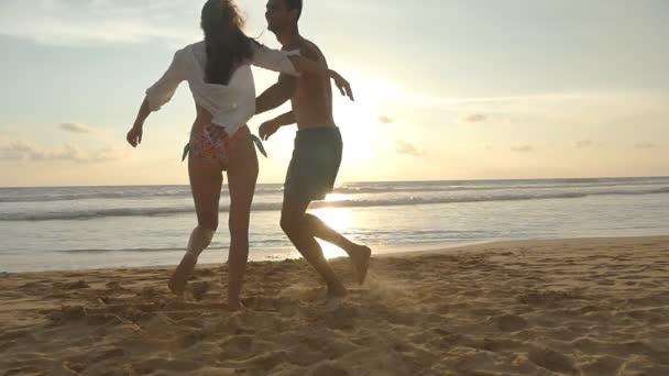 Fiatal pár a strandon, ölelés ember fut és spin-körül a nő a naplemente. Lány ugrik a barátja karját, és ő örvénylő neki-a gyönyörű tengerparton. Érzik magukat együtt a nyaralás. Slow Motion